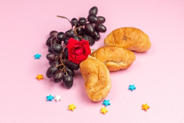 Vue avant de délicieux croissants cuits au four avec garniture de fruits avec des raisins noirs frais sur un bureau rose