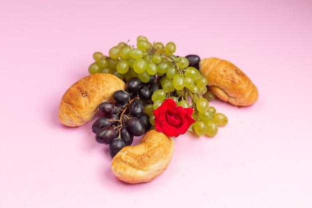 Vue avant de délicieux croissants cuits au four avec garniture de fruits avec des raisins noirs et verts frais sur le bureau rose