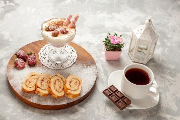 Vue avant de délicieux dessert aux fraises avec des petits pains de fruits sucrés sur un espace blanc