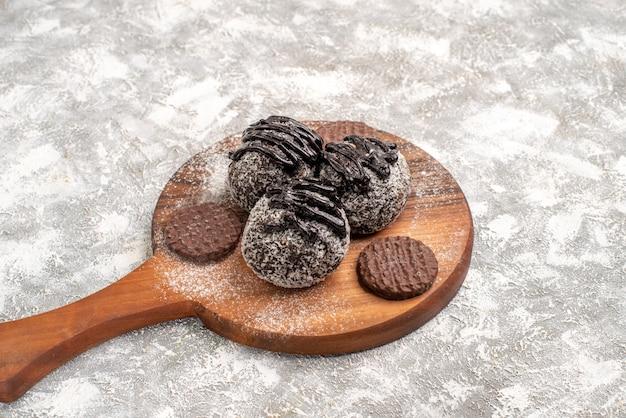 Vue avant de délicieux gâteaux au chocolat avec des cookies sur un espace blanc