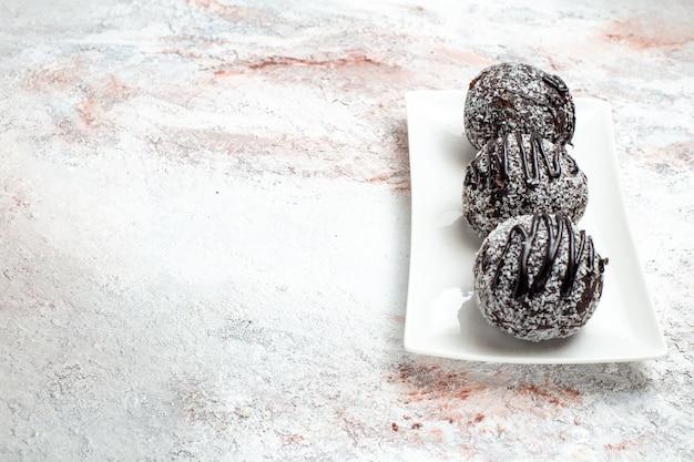 Vue avant de délicieux gâteaux au chocolat avec du glaçage sur la surface blanche-légère biscuit au sucre au chocolat gâteau sucré biscuit cuire au four