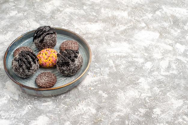Vue avant de délicieux gâteaux aux boules de chocolat avec des biscuits sur un espace blanc clair