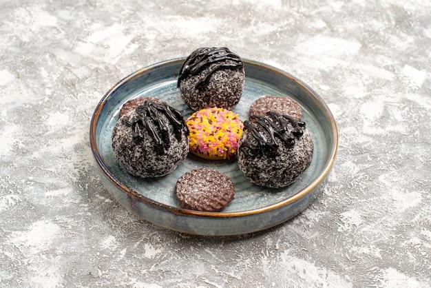 Vue avant de délicieux gâteaux aux boules de chocolat avec des cookies sur un espace blanc