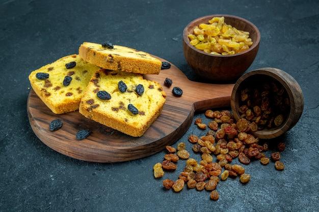Vue avant de délicieux gâteaux aux raisins secs tranchés avec des raisins secs frais sur l'espace bleu foncé