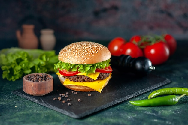 Vue avant de délicieux hamburger de viande aux tomates rouges sur fond sombre