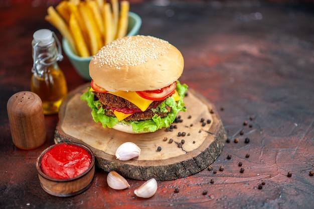 Vue avant de délicieux hamburger de viande avec des frites sur fond sombre