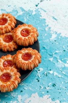 Vue avant de délicieux petits biscuits avec de la confiture à l'intérieur de la plaque noire sur le bureau bleu biscuit biscuit thé de couleur sucre sucré
