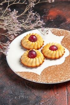 Vue avant de délicieux petits biscuits à l'intérieur de la plaque sur le gâteau de table sombre biscuits sucrés