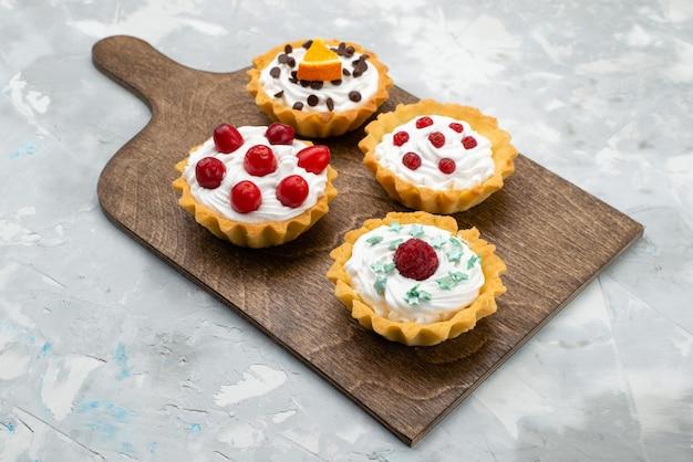 Vue avant de délicieux petits gâteaux à la crème et aux fruits sur la surface grise des fruits sucrés