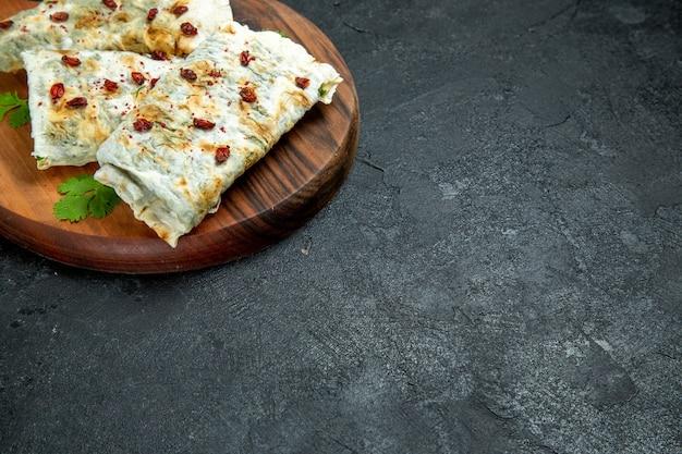 Vue avant de délicieux qutabs roulés des tranches de pâte remplies de vert sur l'espace gris