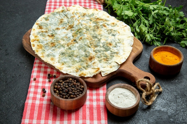 Vue avant de délicieux qutabs de tranches de pâte cuites avec des assaisonnements et des verts sur l'espace gris
