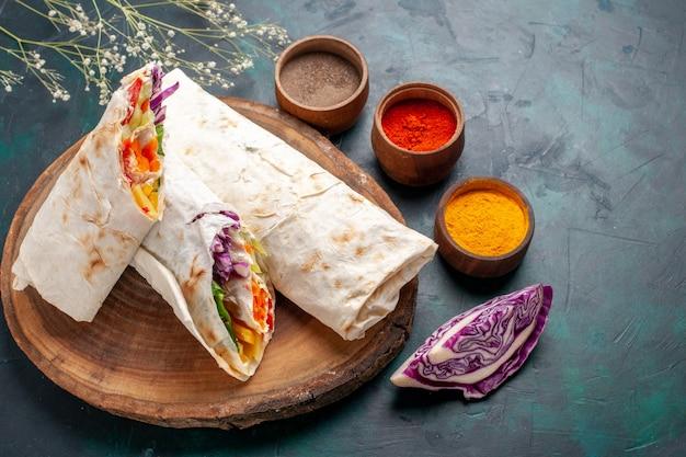 Vue avant de délicieux sandwich à la viande fait de viande grillée à la broche en tranches avec des assaisonnements sur le bureau bleu foncé