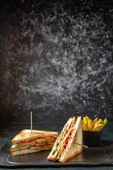 Vue avant de délicieux sandwichs au jambon avec frites surface sombre