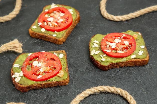 Vue avant de délicieux sandwichs avec du wassabi et des tomates rouges sur le fond gris pain hamburger sandwich repas snack