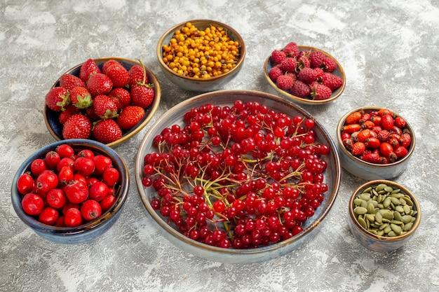 Vue avant différentes baies fraîches à l'intérieur des assiettes sur la table blanche de fruits frais de couleur berry