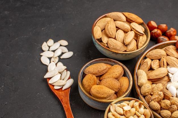 Vue avant de différentes noix noix fraîches à l'intérieur de pots sur une surface sombre