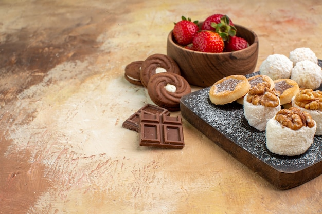 Vue avant différents bonbons avec des biscuits et des fruits sur le gâteau de tarte au sucre aux fruits de bureau léger