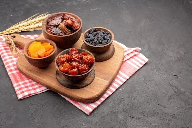 Vue avant différents raisins secs abricots secs et khurmas sur espace gris