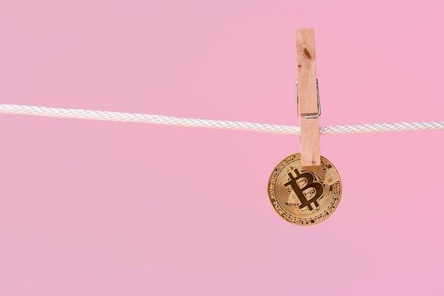 Vue avant du bitcoin tenu par une broche de vêtements sur une corde