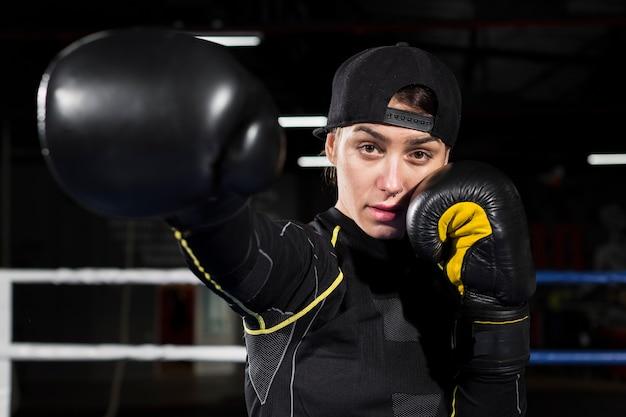 Vue avant du boxeur féminin posant dans des gants de protection