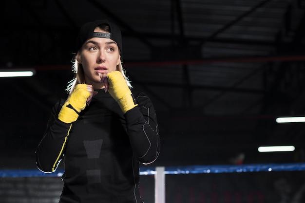 Vue avant du boxeur féminin posant sur le ring avec copie espace
