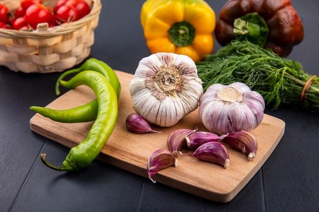Vue avant du bulbe d'ail et des gousses de poivre sur une planche à découper et un panier de tomate poivron bouquet d'aneth sur une surface noire