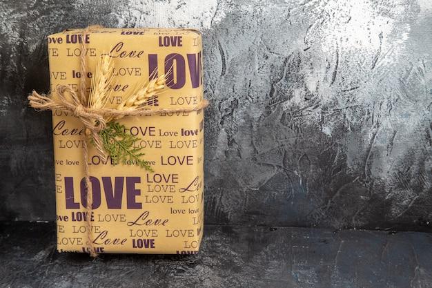 Vue avant du cadeau emballé debout sur le mur sur le côté droit