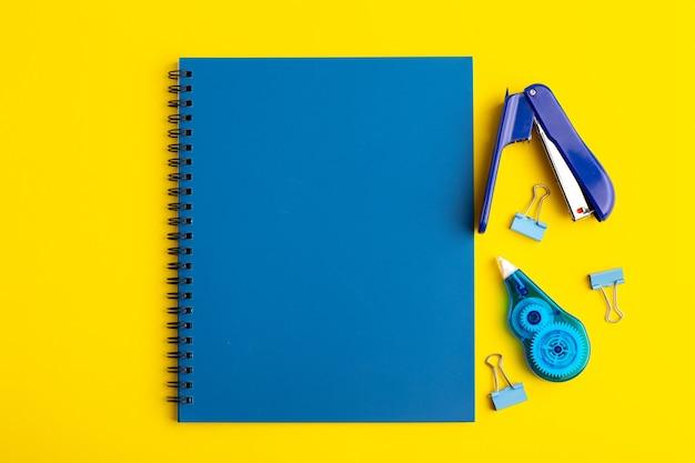 Vue avant du cahier bleu ouvert avec des autocollants sur la surface jaune
