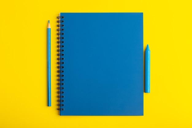 Vue avant du cahier bleu ouvert avec un crayon sur le bureau jaune