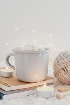 Vue avant du chocolat chaud dans les agendas avec des bougies et du fil
