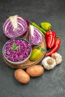 Vue avant du chou rouge avec des légumes frais sur la table grise salade de santé régime mûr