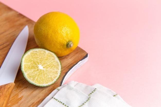 Vue avant du citron frais avec de la chaux en tranches sur le mur rose