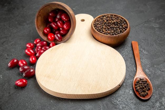Vue avant du cornouiller rouge frais avec du poivre sur l'espace gris