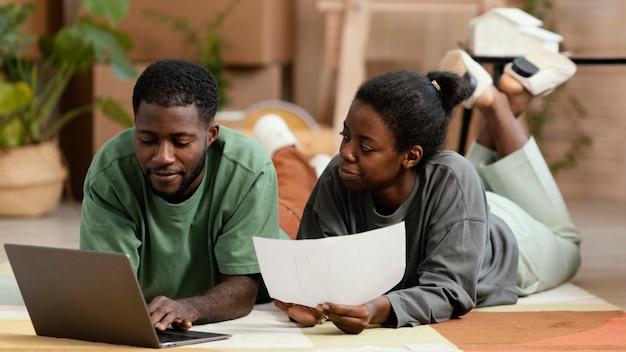 Vue avant du couple à l'étage faisant des plans pour redécorer la maison avec un ordinateur portable