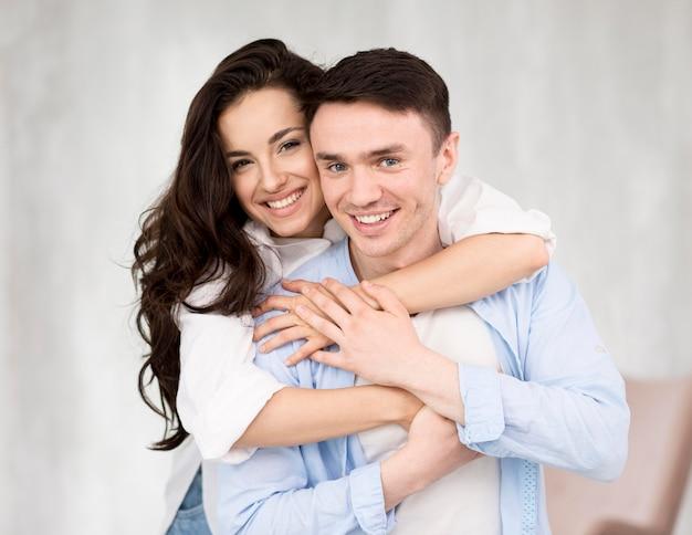 Vue avant du couple souriant posant embrassé