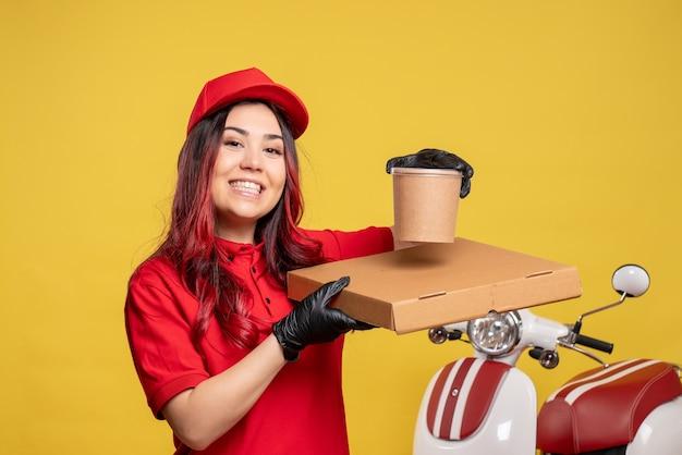 Vue avant du courrier femelle avec boîte de nourriture sur mur jaune