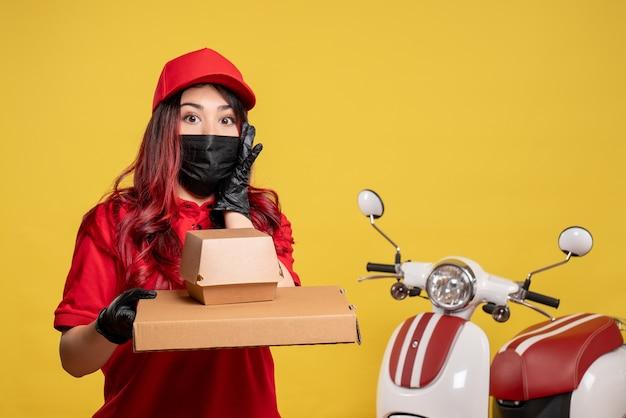 Vue avant du courrier féminin en masque avec livraison de nourriture sur mur jaune