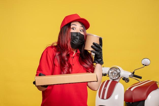 Vue Avant Du Courrier Féminin En Masque Avec Livraison De Nourriture Sur Mur Jaune Photo gratuit