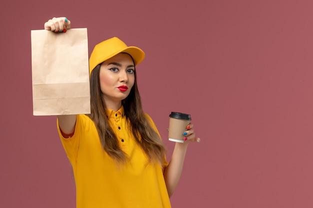 Vue avant du courrier féminin en uniforme jaune et cap tenant la tasse de café de livraison et le paquet de nourriture sur le mur rose