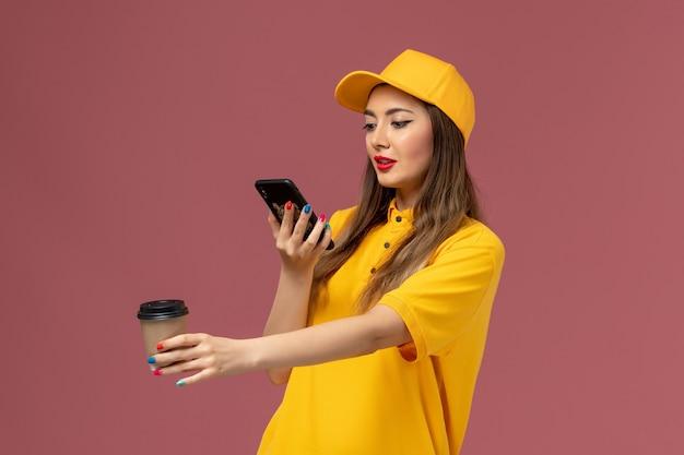 Vue avant du courrier féminin en uniforme jaune et cap tenant la tasse de café de livraison et en prendre une photo sur le mur rose