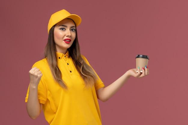 Vue avant du courrier féminin en uniforme jaune et cap tenant la tasse de café de livraison se réjouissant sur le mur rose