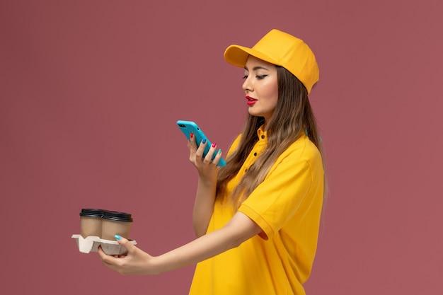 Vue avant du courrier féminin en uniforme jaune et cap tenant des tasses de café de livraison en prenant une photo d'eux sur le mur rose