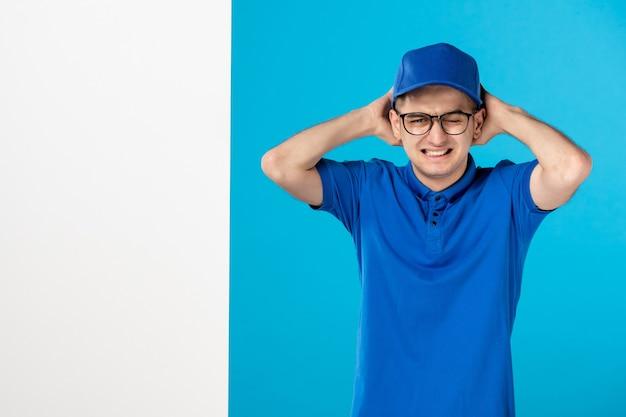 Vue avant du courrier masculin nerveux en uniforme bleu sur fond bleu