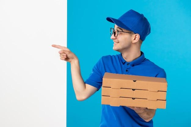 Vue avant du courrier masculin en uniforme bleu avec des boîtes de pizza sur un bleu