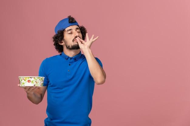 Vue avant du courrier masculin en uniforme bleu et cape tenant un bol de livraison rond sur le mur rose