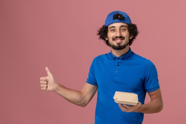 Vue avant du courrier masculin en uniforme bleu et cape tenant peu de colis alimentaires de livraison sur le mur rose