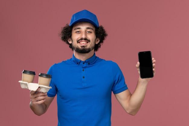Vue avant du courrier masculin en uniforme bleu et capuchon avec livraison tasses à café et téléphone de travail sur ses mains sur le mur rose