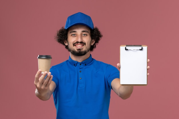 Vue avant du courrier masculin en uniforme bleu et capuchon avec tasse de café de livraison et bloc-notes sur ses mains sur le mur rose