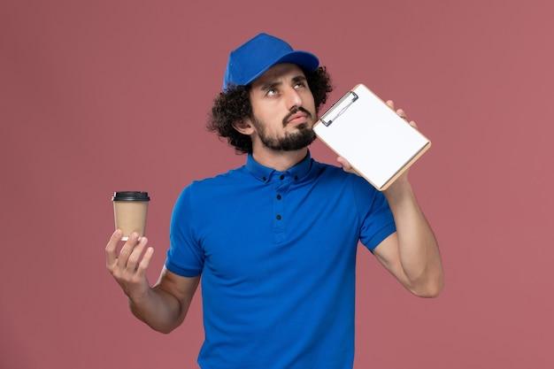 Vue avant du courrier masculin en uniforme bleu et capuchon avec tasse de café de livraison et bloc-notes sur ses mains en pensant sur le mur rose