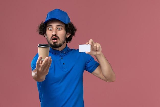 Vue avant du courrier masculin en uniforme bleu et capuchon avec tasse de café de livraison et carte sur ses mains sur le mur rose